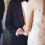 Groom puts ring on bride