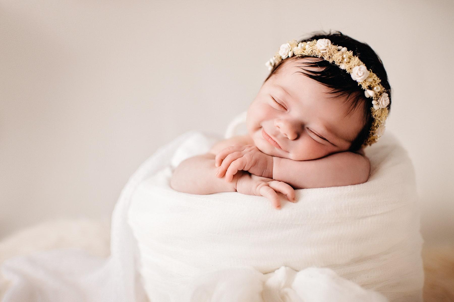newborn in basket smiling