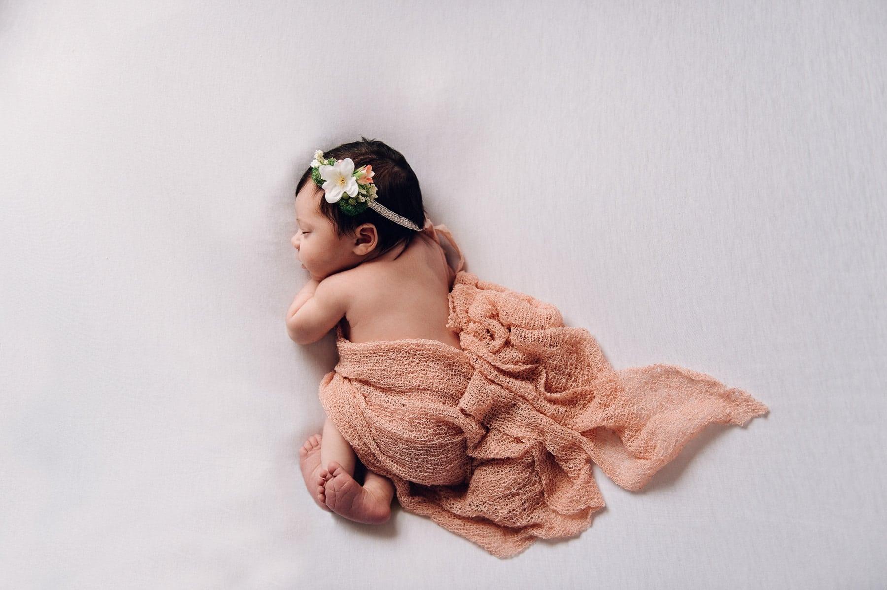 newborn girl in dusty pink wrap